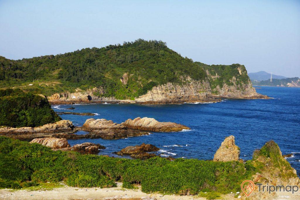 bãi đá cầu mỵ (bãi đá móng rồng), ảnh chụp ngoài trời, bầu trời trong xanh, cây cối xanh tươi trên những đảo gần bãi đá, nước biển xanh