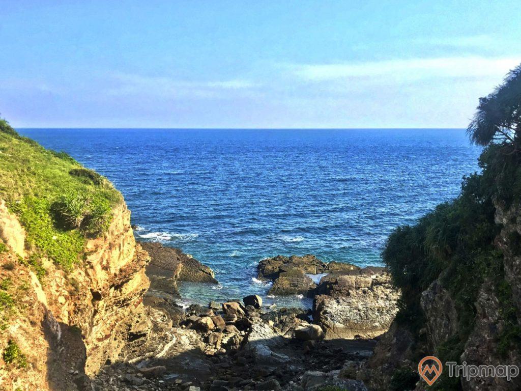 cảnh quan thiên nhiên tại bãi đá cầu mỵ (bãi đá móng rồng), ảnh chụp ngoài trời, bầu trời xanh ít mây, biển ở Cô Tô, cây cối mọc xanh tươi trên đá
