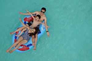 Bể bơi cho khách V.I.P, mặt nước bể bơi màu xanh, 3 người đang nằm trên chiếc phao màu xanh, ảnh chụp từ trên cao, ảnh chụp ban ngày