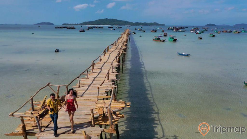 Cây cầu Gỗ dài và lãng mạng trên đảo Cô Tô, một người đàn ông mặc áo vàng nắm tay cô gái váy đỏ đi trên cầu, ảnh chụp ngoài trời, bầu trời nhiều mây, đảo phía xa xa, nhiều chiếc thuyền neo đậu gần cây cầu