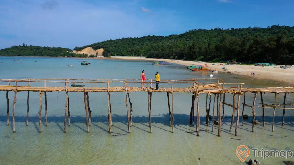 Du khách chụp ảnh trên cây Cầu Gỗ, ảnh chụp ngoài trời, bầu trời xanh ít mây, cây cối trên đảo xanh tươi, một người áo vàng đứng chụp ảnh cho cô gái váy đỏ ở trên cây cầu gỗ, nhiều chiếc thuyền neo đậu gần cây cầu