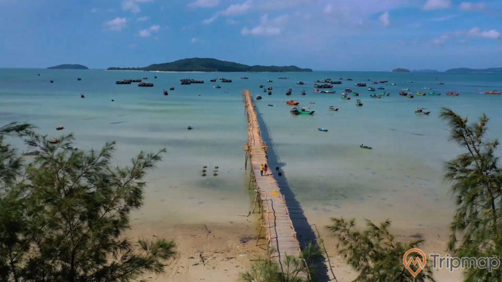 cây cầu gỗ từ bờ biển ra ngoài khơi xa đảo Cô Tô, ảnh chụp từ trên cao, bầu trời xanh nhiều mây, nhiều chiếc thuyền neo đậu gần cây cầu, đảo phía xa xa, ngọn cây phi lao xanh