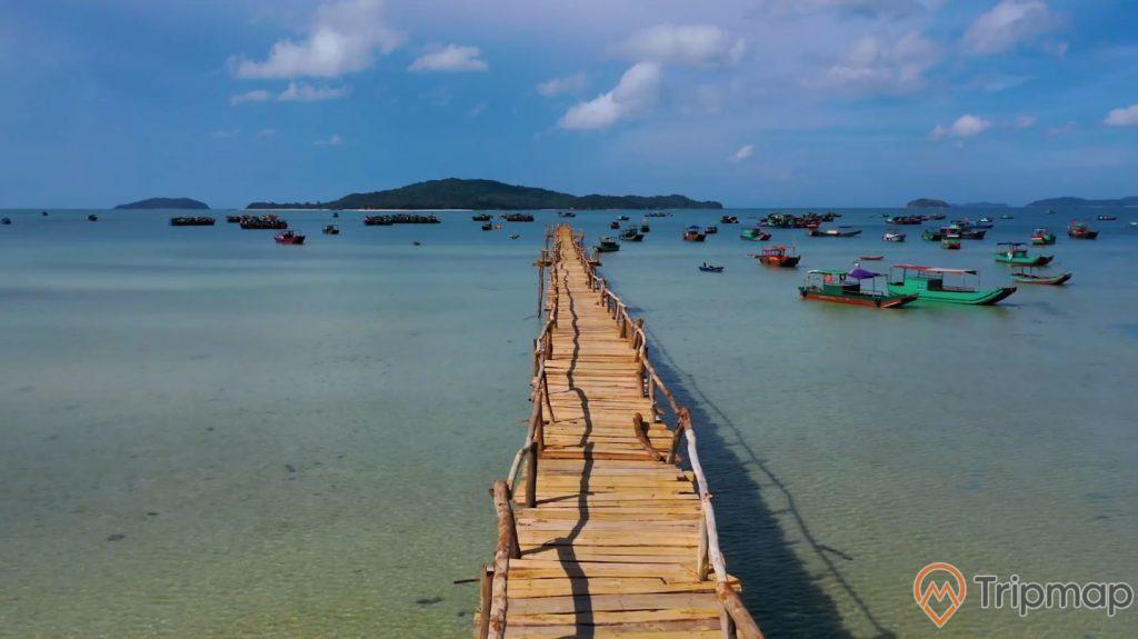 cầu gỗ trên biển, nhiều thuyền bè, phía xa có đảo, ảnh chụp ban ngày, trời xanh, nước biển nông