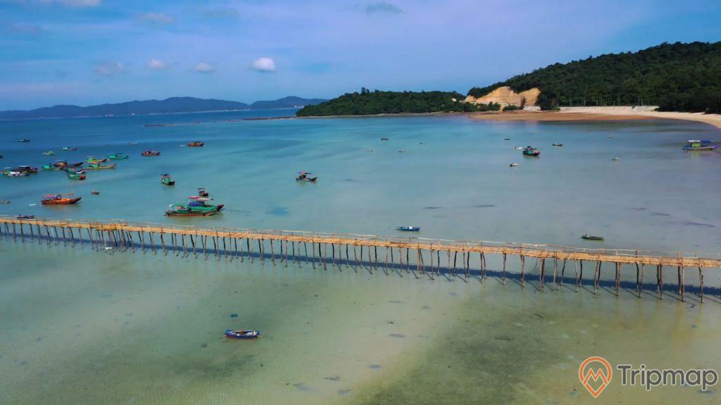 Ảnh chụp mặt bên trái của Cầu Gỗ trên đảo Cô Tô, những chiếc thuyền đang neo đâu gần cây cầu, dãy đảo phía xa xa cây cối xanh tươi, cây cầu gỗ trên mặt bờ biển, bầu trời xanh nhiều mây, ảnh chụp trên cao