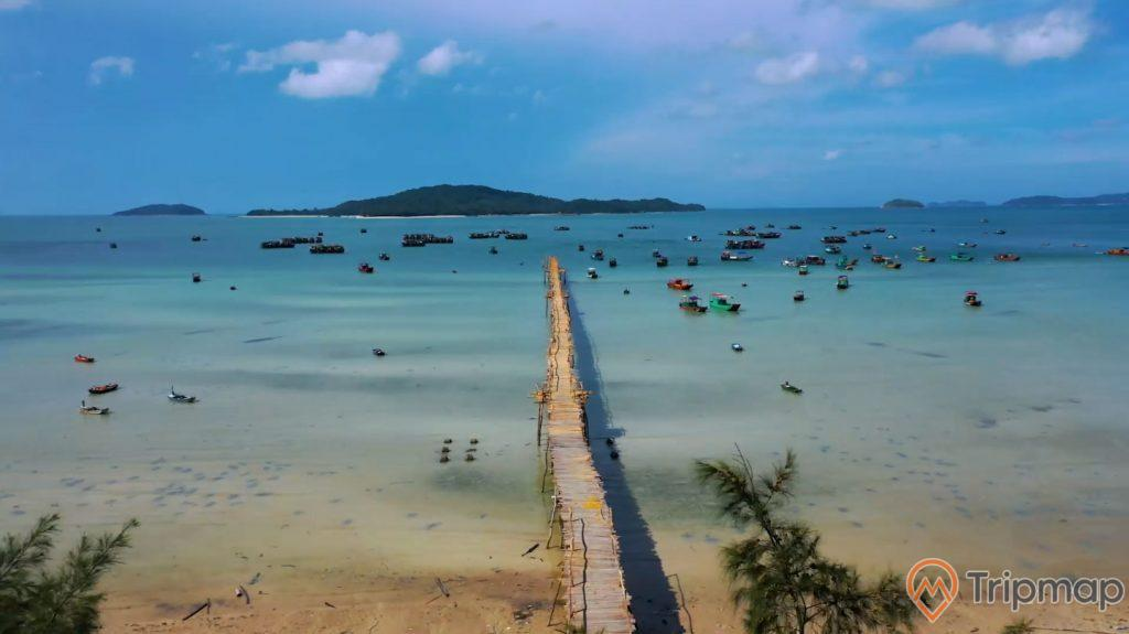 cảnh quan thiên nhiên ở Cầu Gỗ trên đảo Cô Tô, ảnh chụp trên cao, đảo phía xa xa, bầu trời xanh nhiều mây, nhiều chiếu thuyền đang neo đậu và những chiếc thuyền đang đi trên mặt biển