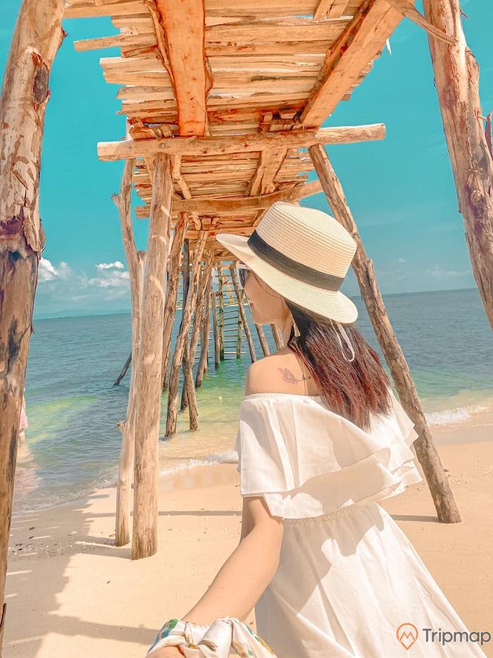 ảnh chụp dưới chân cầu gỗ cô tô, cô gái mặc váy trắng đội mũ trắng, ảnh chụp từ phía đằng sau cô gái, biển xanh, thuỷ triều rút, trời xanh, ảnh chụp ban ngày, trời có nắng