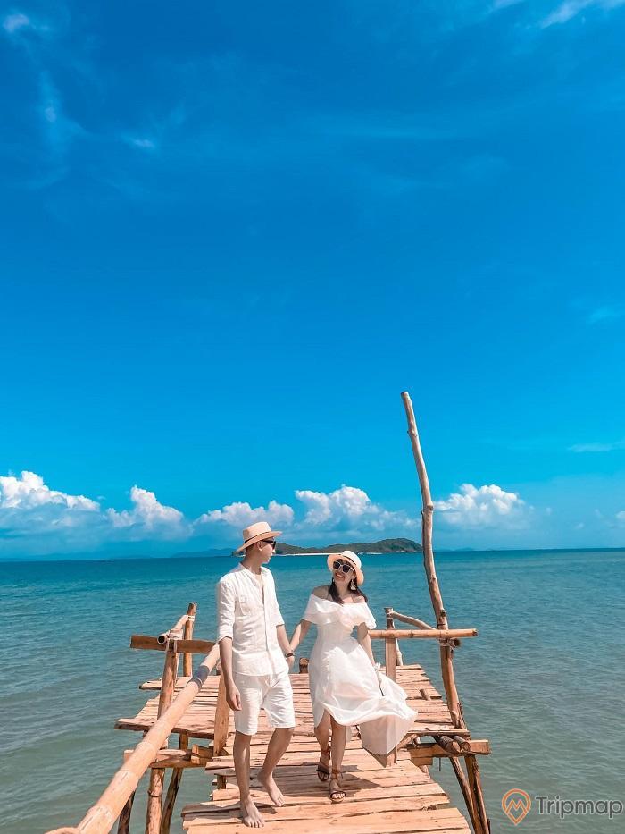 cặp đôi chụp ảnh trên cầu gỗ ngoài biển cô tô, trời xanh, trời nắng, nước biển trong xanh, ảnh chụp ngoài trời, người đàn ông mặc bộ quần áo trắng đội mũ trắng, cô gái mặc váy trắng đội mũ trắng, hai người nắm tay nhau, người đàn ông đi chân trần, cô gái đeo dép xăng đan, cặp đôi hạnh phúc, cô gái tươi cười nắm tay người đàn ông, hai người đeo kính râm, gợn mây trắng phía xa, hòn đảo nhỏ phía xa