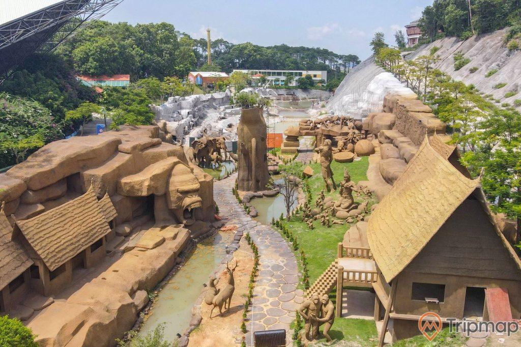 Khu tham quan tương hình tại công viên King Kong, nhiều bức tượng động vật màu nâu, cây cối xanh tươi, , bầu trời có nắng, ảnh chụp từ trên cao