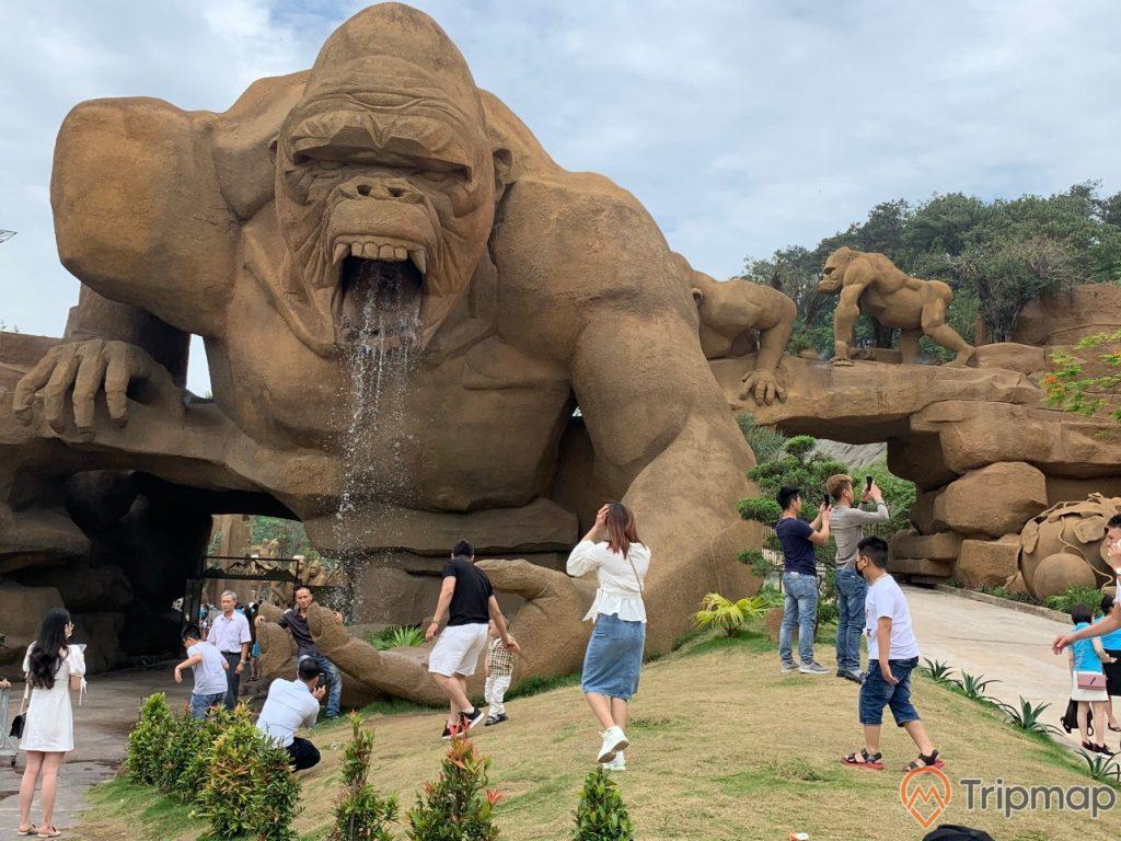 Du khách tham quan khu vui chơi công viên King Kong, tượng King Kong khủng lồ, mọi người đang đứng chụp ảnh tạo dáng gần tượng King Kong, bầu trời nhiều mây, ảnh chụp ngoài trời