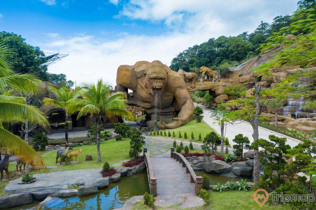 Bức tượng con King Kong khủng lồ tại công viên King Kong, mấy con hươu dưới gốc cây dừa gần dòng nước suối, cây cầu qua dòng nước, cây cối xanh tươi trong công viên King Kong, bầu trời xanh có nhiều mây, ảnh chụp ngoài trời