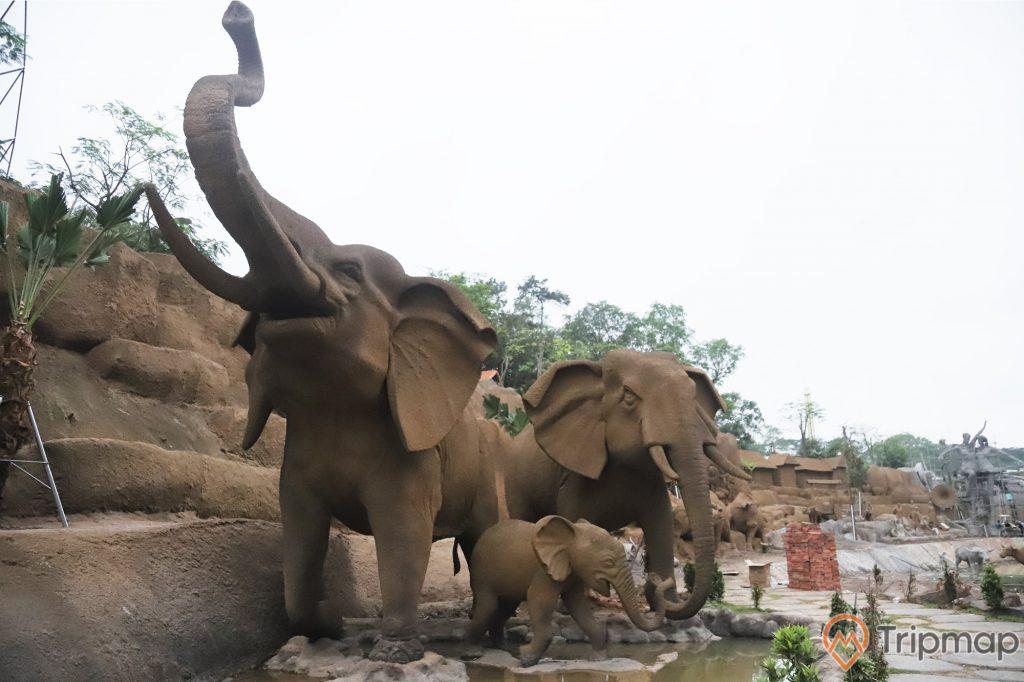 Tượng 3 con voi đang uống nước tại công viên King Kong, cây cối xanh tươi phía xa xa, ảnh chụp ngoài trời