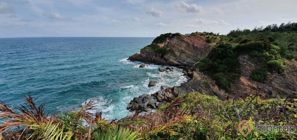 Đảo Cô Tô, nhiều cây xanh, mặt nước biển màu xanh, trời nhiều mây, ảnh chụp ban ngày