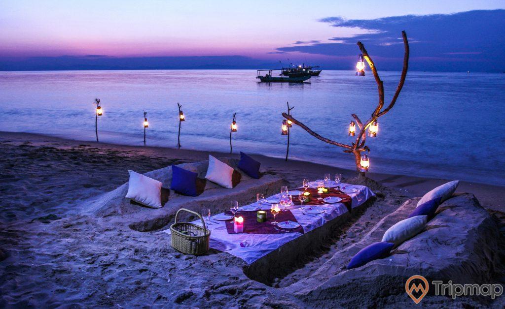Cắm trại buổi tối tại đảo Cô Tô con, bầu trời đang tối dần, những chiếc đèn treo trên cành cây khô, con thuyền gần bờ biển cô tô con