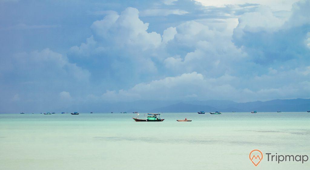 Những chiếc thuyền đang đi ngoài biển gần đảo Cô Tô con, bầu trời nhiều mây, ảnh chụp ngoài trời