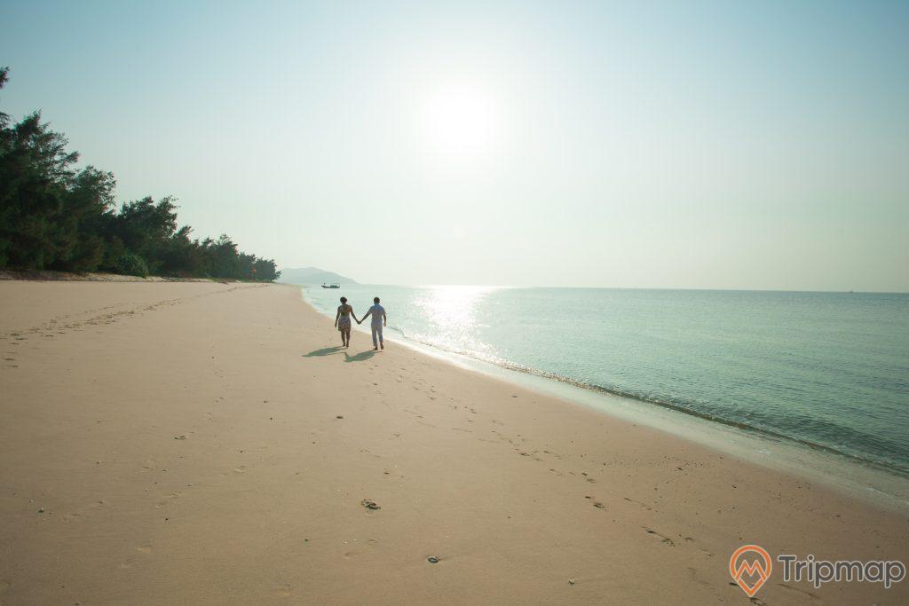 Cảnh bãi biển đẹp tại đảo Cô Tô con, người đang nắm tay nhau đi trên bãi biển, ảnh chụp đứng trên bãi biển, cây cối gần bờ biển, bầu trời nắng chói