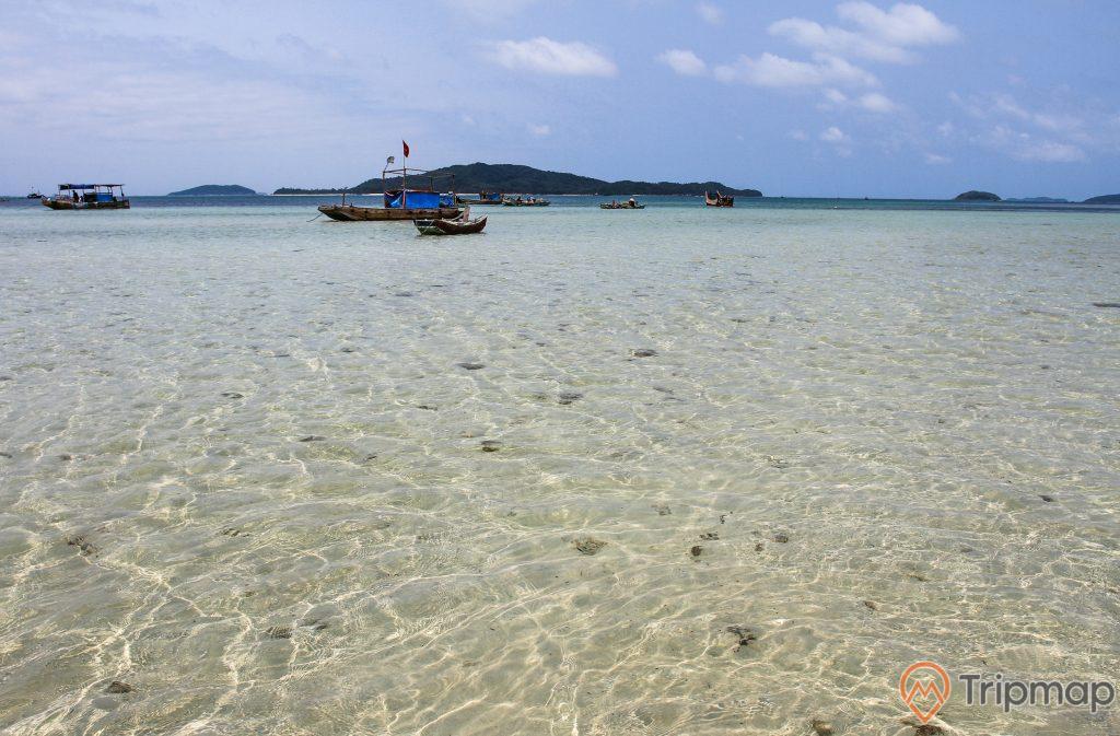 Nước biển trong veo tại bờ biển đảo Cô Tô con, nhiều chiếc thuyền đang neo đậu, bầu trời xanh nhiều mây, đảo phía ngoài xa, ảnh chụp ngoài trời