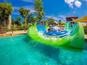 Đảo hải tặc, nhiều người đang ngồi trên chiếc phao màu xanh, ống trượt màu xanh, mặt nước màu xanh, nhiều cây xanh bên cạnh, trời nắng, trời xanh nhiều mây, ảnh chụp ban ngày