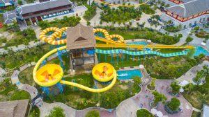 Đảo hải tặc, ống trượt màu vàng, ống trượt màu xanh, nhiều cây xanh xung quanh, nhà có mái màu nâu, ảnh chụp từ trên cao, ảnh chụp ban ngày, công viên nước