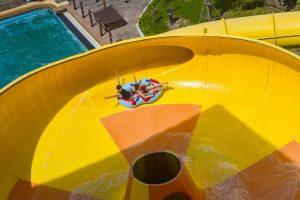 Đảo hải tặc, 2 người đang ngồi trên chiếc phao màu xanh, ống trượt màu vàng, trời nắng, bể bơi phía dưới, ảnh chụp từ trên cao, ảnh chụp ban ngày