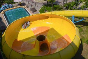 Đảo hải tặc, 2 người đang ngồi trên chiếc phao màu xanh, ống trượt màu vàng, bể bơi phía dưới, trời nắng, ảnh chụp từ trên cao, ảnh chụp ban ngày