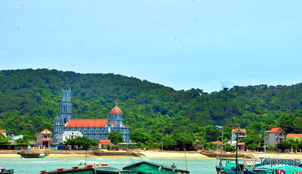 Đảo Thanh Lân, nhà thờ giáo họ, ngọn núi nhiều cây xanh phía xa, nhiều thuyền đang đỗ trên bãi biển, trời nắng, ảnh chụp ban ngày