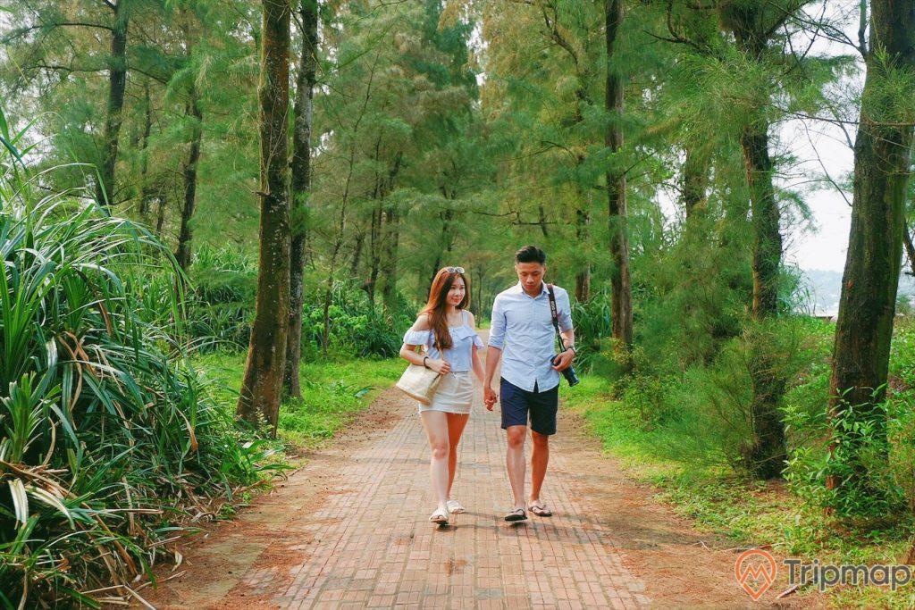 Cặp đôi tình nhân đi trên đường tình yêu Cô Tô, cô gái áo xanh vay trắng đeo túi nắm tay chàng trai áo xanh quần short đen đeo máy ảnh đang đi, cây cối hai bên đường đi xanh tươi