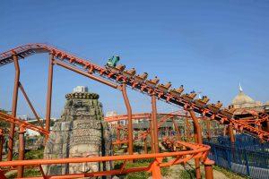 Hành Trình Bí Ẩn, Dragon Park, đường ray màu cam, tảng đá có hoa văn, hàng rào sơn màu xanh, trời xanh, trời nắng, ảnh chụp ban ngày