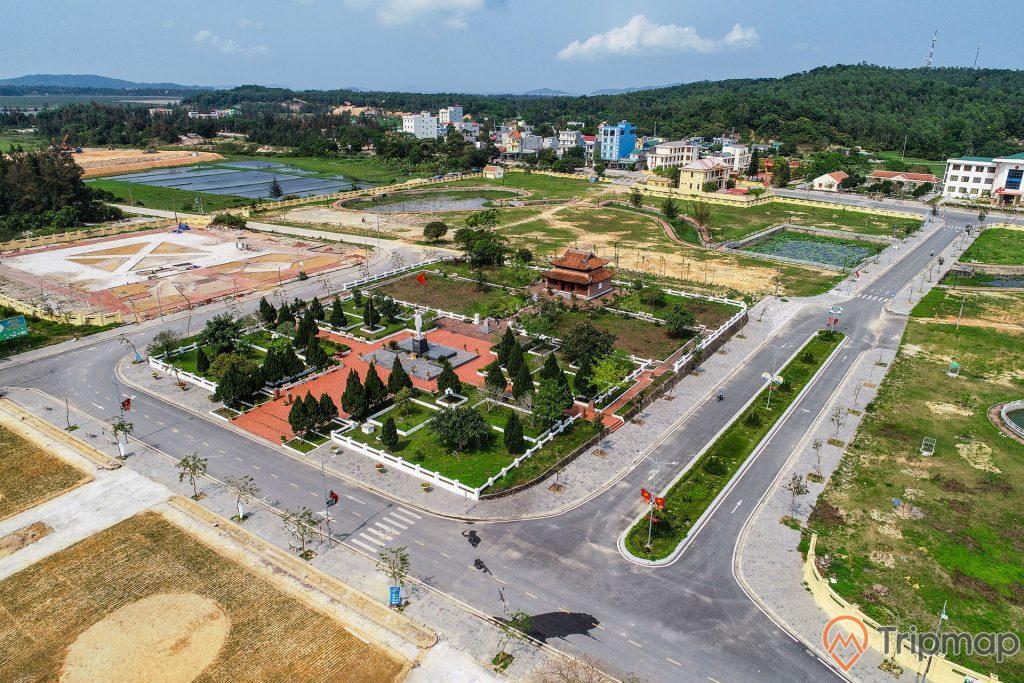 ảnh chụp khu di tích lưu niệm Hồ Chỉ Tịch trên đảo Cô Tô từ trên cao, cây cối xanh tươi, ngôi nhà cao tầng phía xa gần ngọn đồi cây cối xanh tươi, con đường giao thông
