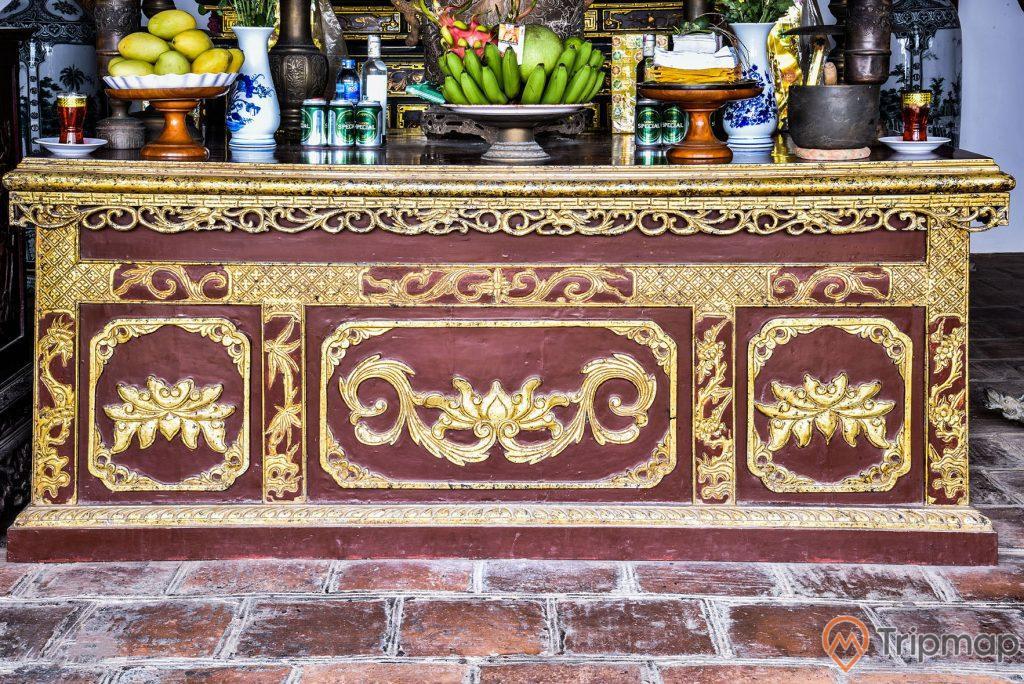 """Bàn thờ trong đền thờ bác Hồ tại khu di tích lưu niệm Hồ Chủ tịch trên đảo Cô Tô, trên bàn thờ có """" 1 đĩa ngũ quả, 1 đĩa xoài, 1 đĩa tiền vàng mã, 2 lọ hoa, 2 cốc nến, nhiều lon bia sài gòn"""", bàn thờ màu đỏ hoạ tiết đẹp màu vàng"""