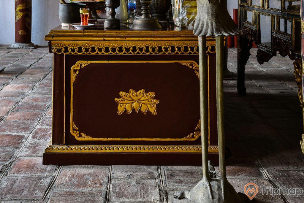 Mặt hông của bàn thờ trong đền thờ Bác Hồ tại khu di tích lưu niệm Hồ Chủ tịch trên đảo Cô Tô, ảnh chụp trong nhà, bàn thờ hoạ tiết màu vàng, trên mặt bàn thờ có cốc nến màu đỏ