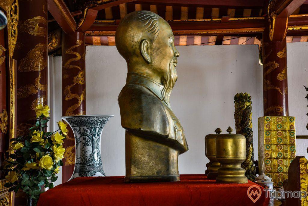 Mặt bên phải bức tượng Bác Hồ trong đền thờ Bác Hồ tại khu di tích lưu niệm Hồ Chủ tịch trên đảo Cô Tô, tượng đồng bác Hồ và 3 lư bằng đồng trên bàn màu đỏ, chiếc lục bình và bình hoa màu vàng cạnh bàn thờ, ảnh chụp trong đền thờ Bác Hồ
