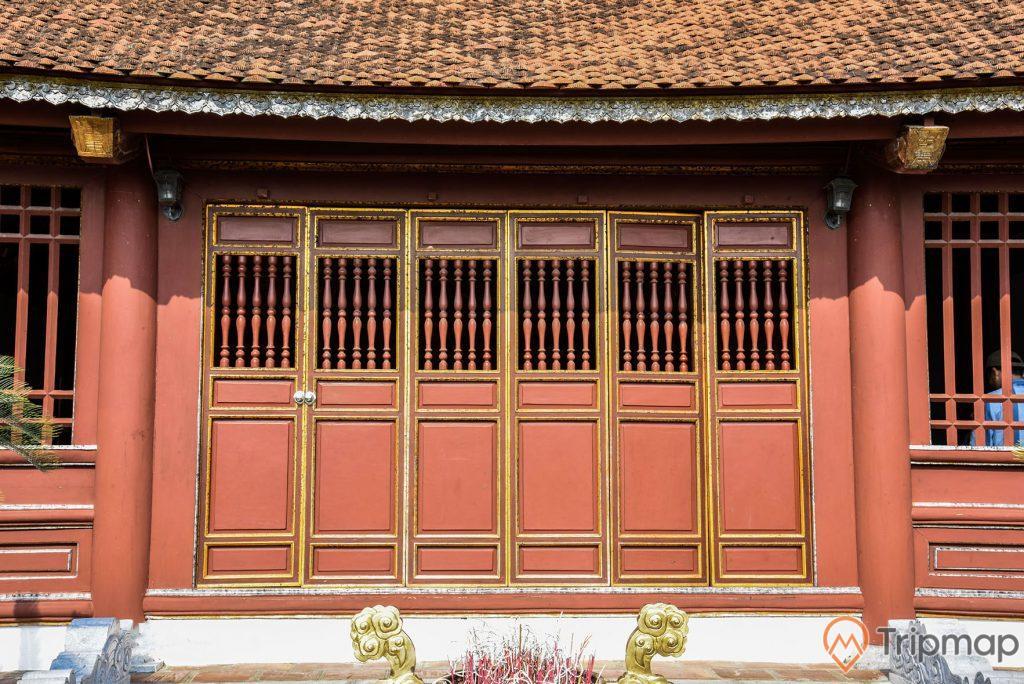 Cửa chính vào đền thờ bác Hồ tại khu di tích lưu niệm Hồ Chủ tịch trên đảo Cô Tô, cửa 8 cánh màu đỏ của đền thờ đang đóng và mái ngói màu đỏ đã cũ, một góc của chiếc lư hương ngoài trời phía trước cửa đền thờ, ảnh chụp ngoài trời
