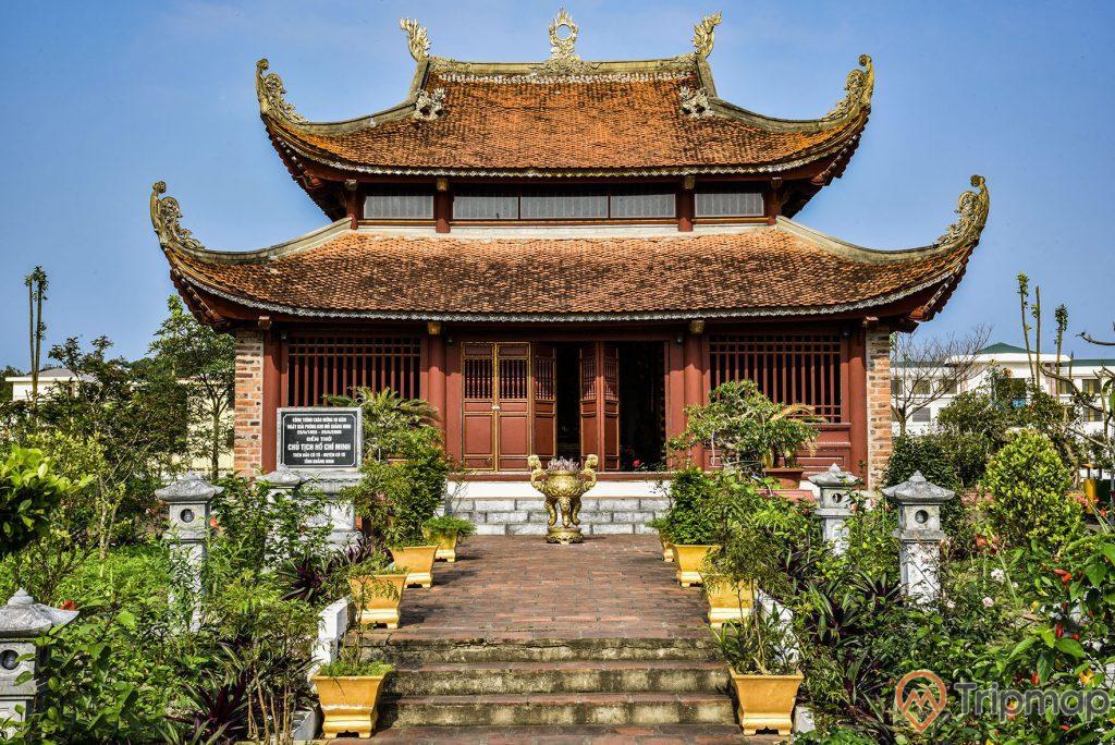 Mặt tiền phía trước của đền bác Hồ tại khu di tích lưu niệm Hồ Chủ tịch trên đảo Cô Tô, lư hương màu vàng ở chính giữa đền thờ, đền thờ bác hồ mái cong 2 tầng ngói màu đỏ, chậu cây và cây cối hai bên lối đi xanh tươi, ảnh chụp ngoài trời, bầu trời trong xanh