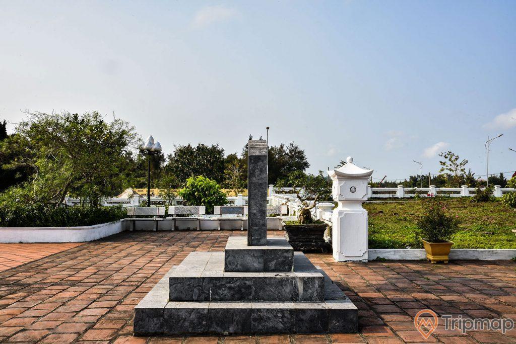 Mặt cạnh phải tấm bia đá ở đền thờ bác Hồ tại khu di tích lưu niệm Hồ Chủ tịch trên đảo Cô Tô, cây cối trong khuôn viên xanh tươi, hàng ghế đá ở phía góc sân, bầu trời đẹp trong xanh và có nhiều mây trắng, ảnh chụp ngoài trời