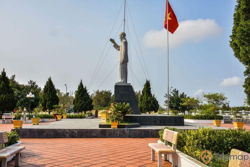 Ảnh chụp bên trái bức tượng Bác Hồ tại khu di tích lưu niệm Hồ Chủ tịch trên đảo Cô Tô, cây cối trong khuôn viên xanh tươi, cột cờ quốc kỳ Việt Nam đang bay phất phới, ghế đá đặt cạnh bồ hoa, bầu trời nhiều mây, ảnh chụp ngoài trời