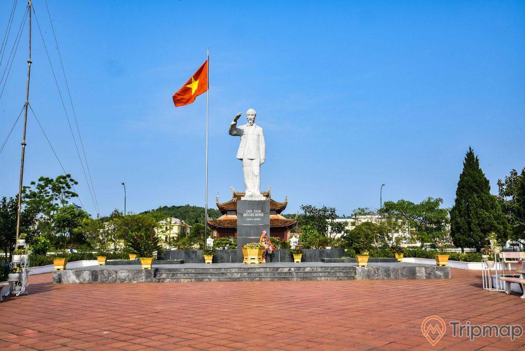 Đài tưởng niệm bác Hồ tại khu di tích lưu niệm Hồ Chủ tịch trên đảo Cô Tô, bầu trời trong xanh, bức tượng bác hồ đứng đang giơ tay màu trắng, cột cờ lá quốc kỳ Việt Nam đang bay phất phới, cây cối trong khuôn viên xanh tươi, phía sau là đền thờ bác Hồ, ảnh chụp ngoài trời