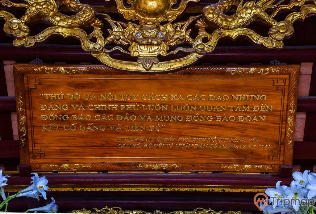 """Tấm bảng khắc ghi lời nói của chủ tịch Hồ Chí Minh trong đền thờ Bác Hồ tại di tích lưu niệm Hồ Chủ tịch trên đảo Cô Tô, tấm bảng bằng gỗ khắc lại lời trích của chủ tịch Hồ Chí Minh """"thủ đô Hà Nội tuy cách xa các đảo nhưng đảng và chính phủ luôn luôn quan tâm đến đồng bào các đảo và mong đồng bào đoàn kết cố gắng và tiến bộ"""" với cán bộ bộ đội và nhân dân cô tô ngày 19-5-1961, ảnh chụp trong đền thờ bác Hồ, hoa loa kèn mày xanh"""