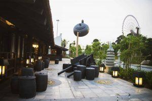 Mộc trà quán, nền gạch màu xám, nhiều đèn phát sáng, nhiều cây xanh, mô hình bộ ấm chén, vòng quay mặt trời ở phía xa, ảnh chụp ban ngày