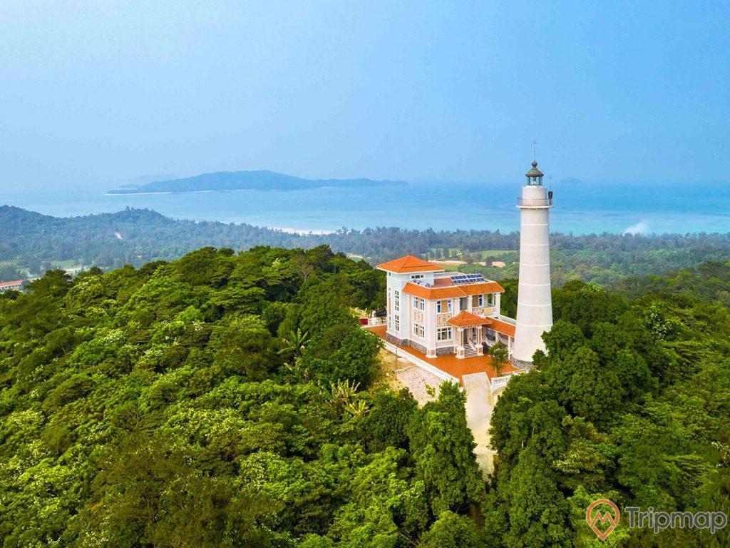 Toàn cảnh ngọn hải đăng Cô Tô mới, ảnh chụp trên cao, cây cối trên ngọc đồi xanh tươi, ngôi nhà màu trắng mái ngói màu đỏ và ngọc hải đăng màu trắng, bầu trời trong xanh