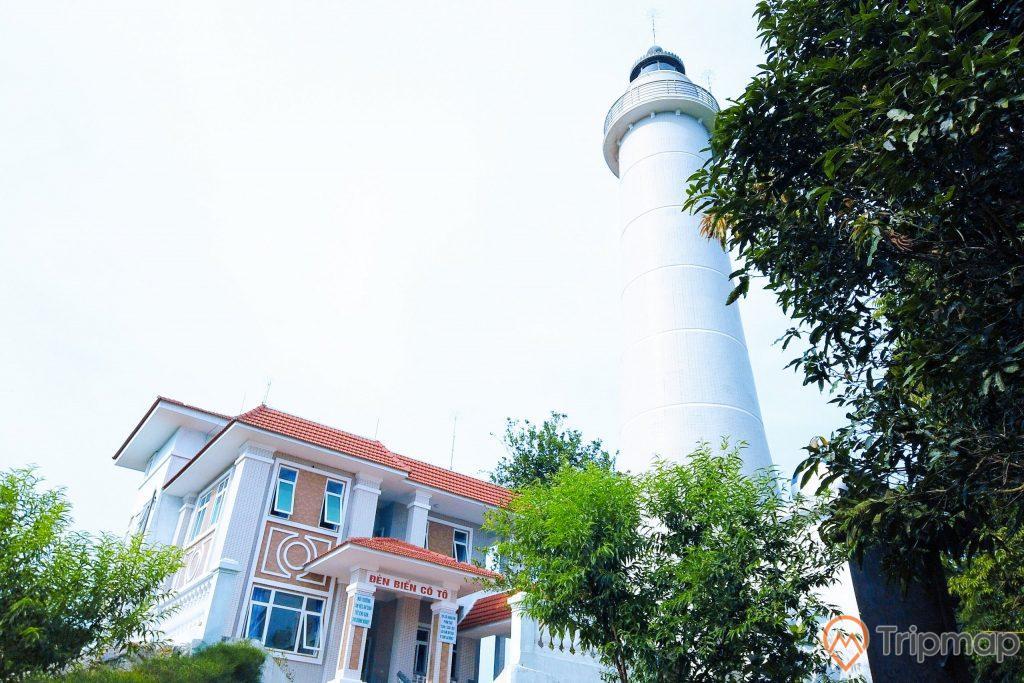 Khung cảnh ngọn hải đăng Cô Tô mới, cây cối xanh tươi, bầu trời nhiều mây trắng, cột đèn hải đăng màu trắng và ngôi nhà mái ngói màu đỏ