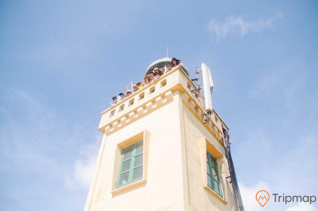 Ảnh chụp ngọn hải đăng Cô Tô, bầu trời xanh ít mây, ảnh chụp đứng dưới, mọi người đứng trên ngọn đèn biển nhìn xuống dưới, logo Tripmap
