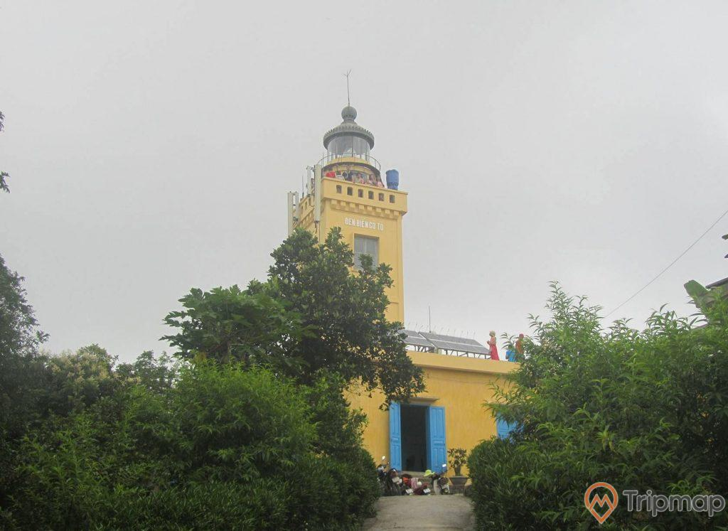 Ngọn hải đăng Cô Tô màu vàng, bầu trời nhiều mây, cây cối xanh tươi, ảnh chụp ngoài trời