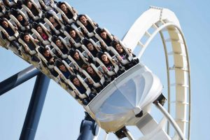 Phi Long Thần Tốc, đường ray sơn màu trắng, nhiều người đang ngồi trên ghế của trò chơi, trời nắng, ảnh chụp ban ngày
