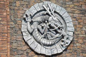 Phi Long Thần Tốc, nền gạch màu đỏ biểu tượng hình rồng bằng đá màu xám, ảnh chụp ban ngày
