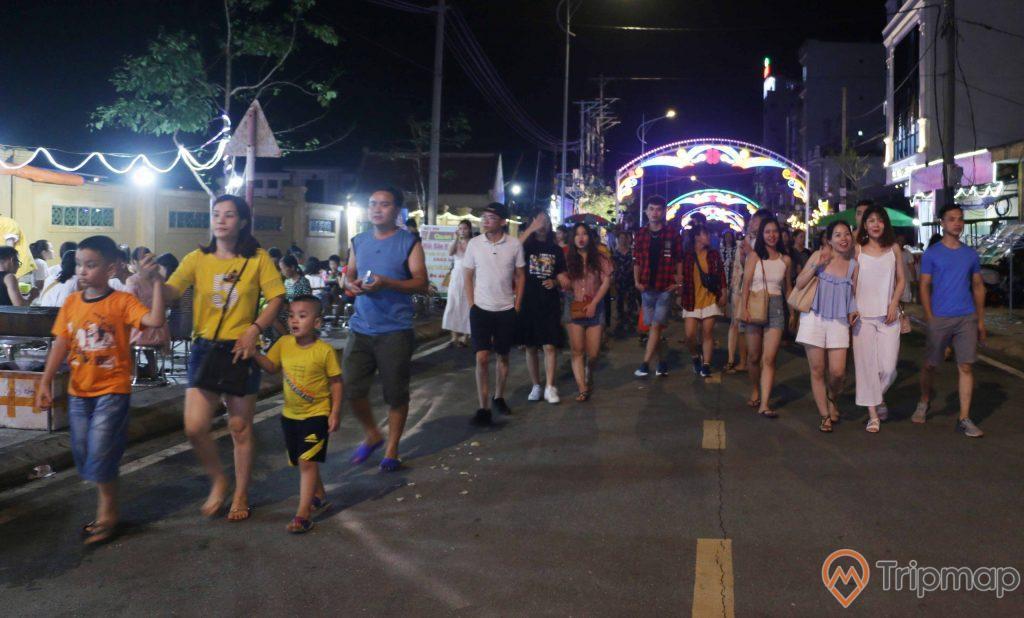 Mọi người đang đi bộ tại khu phố đi bộ ký con, ảnh chụp vào buổi tối, ánh sáng của ánh đèn cửa tiệm và đèn đường
