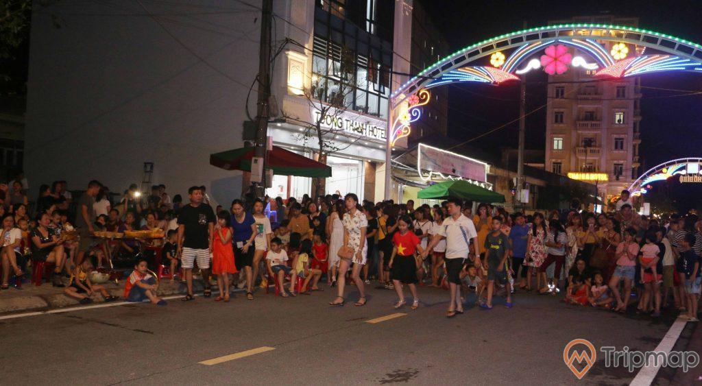 Mọi người tập trung đông ở khu phố đi bộ Ký Con, nhóm người đang đi và đang đứng trên đường, nhóm người khác ngồi trên vỉa hè, ảnh chụp vào buổi tối, đèn điện sáng vào buổi tối