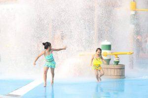 Hai đứa trẻ chơi đùa bên trò Quốc đảo kì diệu, ảnh chụp ngoài trời, một bé gái mặc trang phục xanh và một bé gái trang phục màu vàng đang chạy trong khu vui chơi, trò chơi nước