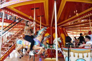 Royal Carousel, Đu Quay Kỳ Diệu, mô hình ngựa, người phụ nữ đang cưỡi ngựa, trụ quay màu nâu, ảnh chụp ban ngày