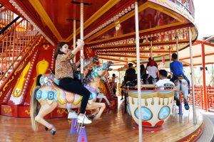 Royal Carousel, Đu Quay Kỳ Diệu, mô hình ngựa màu nâu, người phụ nữ cưỡi mô hình ngựa, trụ quay màu nâu, ảnh chụp ban ngày