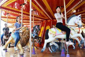 Royal Carousel, Đu Quay Kỳ Diệu, người phụ nữ mặc áo xám đang cưỡi mô hình ngựa, mô hình sư tử màu vàng, trụ quay màu nâu, ảnh chụp ban ngày